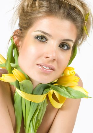 Close-up beautiful fresh young blonde model with tulips flowers around her neck photo