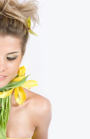 Close-up fresh funny blond half face with beautiful make-up with tulips aroung her neck photo