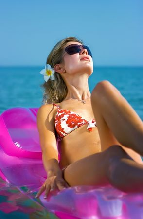 Beautiful blonde girl floating on inflatable raft in the sea photo
