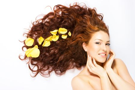 Close-up beautiful luxury fresh bright young lady smiling in studio shot with rose petals in her red (brown) long hair