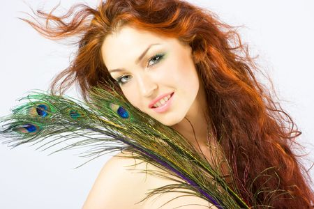 Close-up beautiful luxury fresh bright young lady smiling in studio shot with beautiful make-up with peacock feathers with red (brown) long hair photo