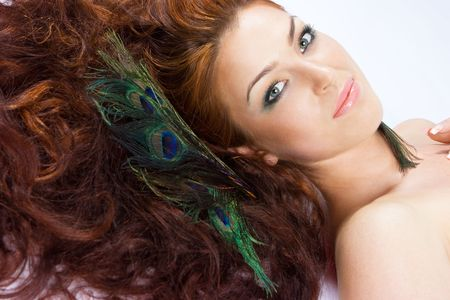 Close-up beautiful luxury fresh bright young lady smiling in studio shot with beautiful make-up with peacock feathers with red (brown) long hair Stock Photo - 5454874