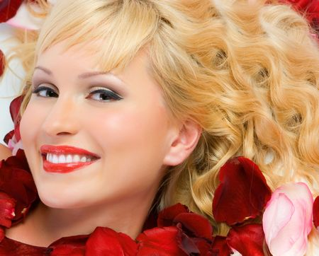 Close-up beautiful fresh young blonde smiling with red and pink rose petals with bright make-up in studio shot photo