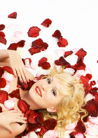 Close-up beautiful fresh young blonde smiling with red and pink rose petals with bright make-up lying in studio shot photo