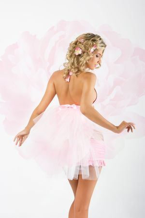 Beautiful fresh young blonde woman in pink clothes in flowers in her hair with peony on white background