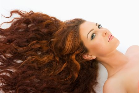 Close-up beautiful luxury fresh bright young lady lying in studio shot with  in her red (brown) long hair Stock Photo