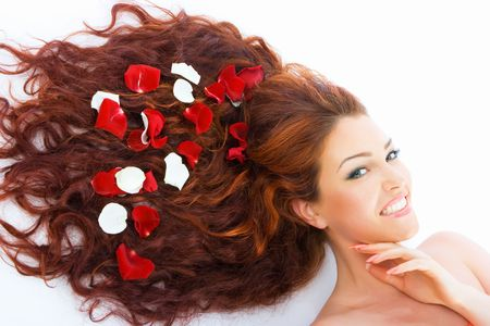 Close-up beautiful luxury fresh bright young lady lying in studio shot with rose petals in her red long hair photo