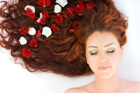 人間の髪の毛: クローズ アップの美しい高級新鮮な明るい若い女性彼女の赤い長い髪にバラの花びらで撮影スタジオで横になっています。