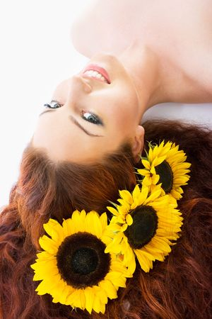 red haired: Close-up beautiful luxury fresh bright young lady in studio shot with sunflowers in her red long hair Stock Photo