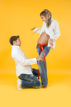 Young couple waiting for a baby on yellow background photo