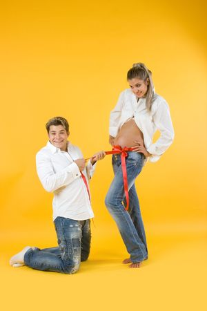 Two young parents waiting for a child on yellow background Stock Photo - 5454796