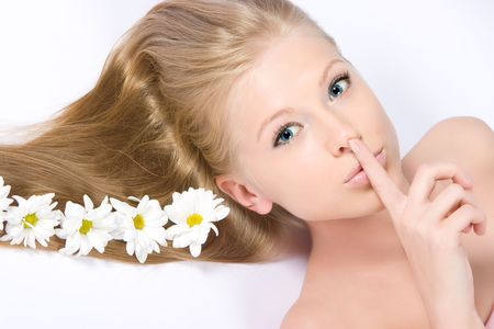 Close-up beautiful fresh girl with flowers on her long blond hair keeping the silence photo
