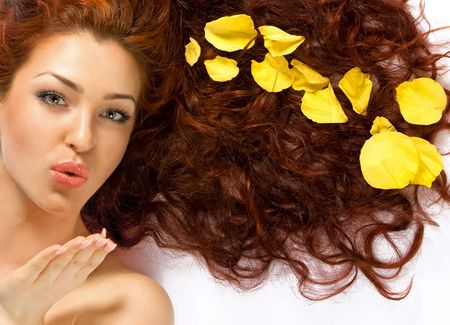 Close-up beautiful fresh red-haired lady with yellow petals in her hair blowing a kiss