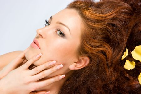 Close-up beautiful red-haired lady with yellow petals in her hair and beautiful manicure Stock Photo