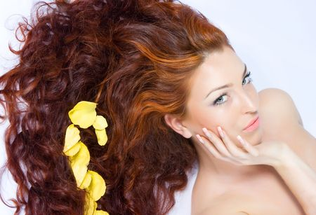 Close-up beautiful fresh luxury lady with yellow petals in her long red hair