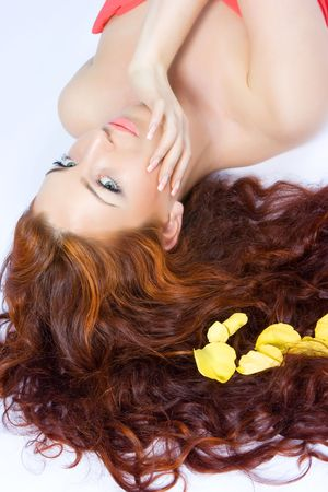 Close-up beautiful fresh luxury lady with yellow petals in her long red hair photo