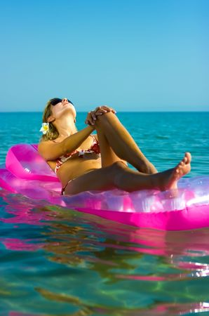 Young blonde girl floating on inflatable raft in the sea photo