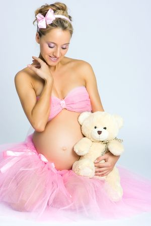 Beautiful young pregnant blonde woman in studio shot holding a teddy bear toy on gray background photo