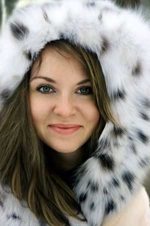 Close-up beautiful young lady in fur cowl in the winter photo