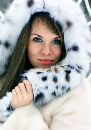 Close-up beautiful brunette lady in fur cowl in the winter photo