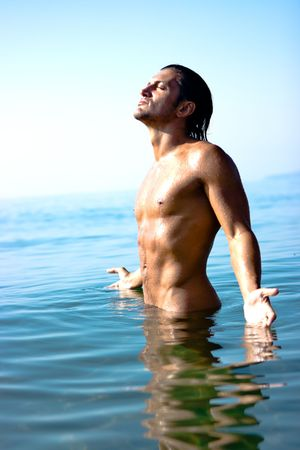 Male athlete with very muscular figure standing in sea water photo