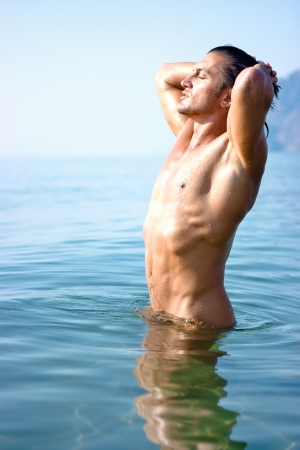 Muscular man relaxing standing in the sea water Stock Photo