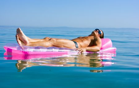 Muscular handsome man in sunglasses relaxing in the sea on inflattable raft