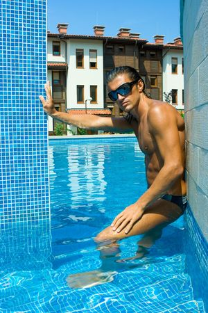 Muscular handsome man in sunglasses standing in the swimming pool photo