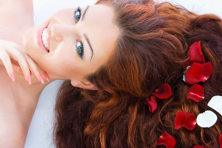 hair spa: Close-up beautiful luxury fresh bright young lady lying in studio shot with rose petals in her red (brown) long hair
