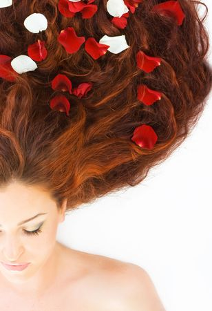 Close-up beautiful luxury fresh bright young half face in studio shot with rose petals in her red (brown) long hair photo