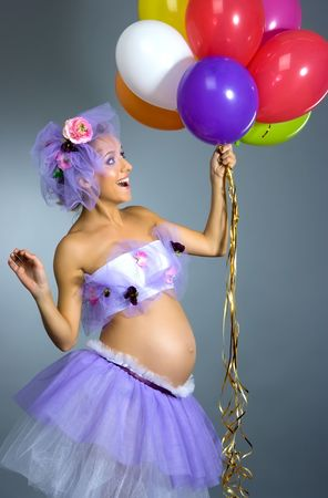 Young beautiful pregnant woman in violet dress with multicolor balloons in studio shot on gray background photo