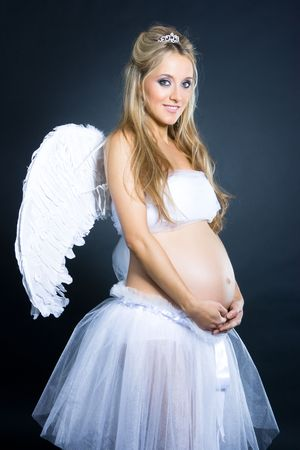awaiting: Beautiful young pregnant girl with angel wings standing on black background Stock Photo