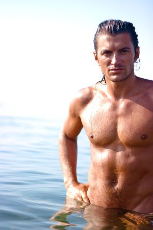 mounts: Muscular man standing in the sea water Stock Photo