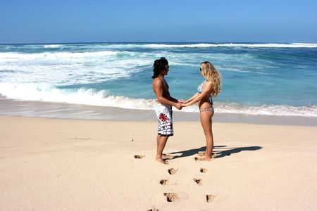 Two lovers standing on the sand beach photo