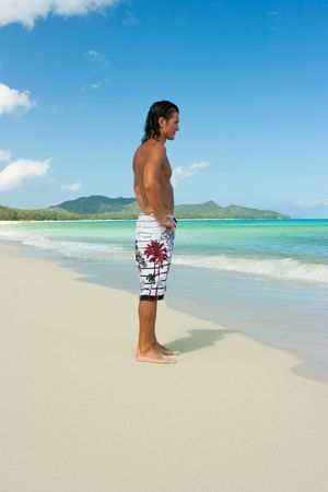 Man standing on sand beach and looking on surf photo