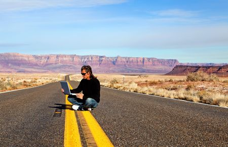 Man in sunglasses sitting on the road with computer
