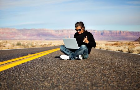 Man in sunglasses sitting on the road with laptop photo