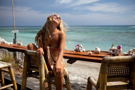 woman beach dress: Blonde girl in the bar on the beach of Bali Stock Photo