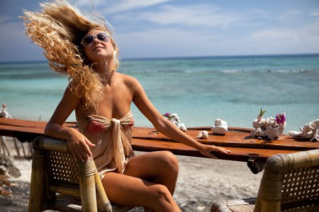 Blonde girl in the bar on the beach of Bali Stock Photo