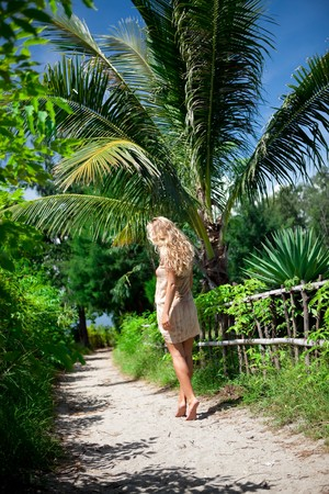 Girl walking on the road to jungle photo