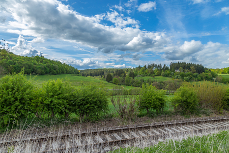 Scenic landscape with blue puffy clouds sky and train rail track green trees and meadows on a hill