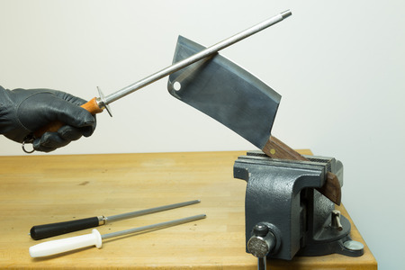 Black glove hand with sharpening steel sharping a rustic cleaver held by a vise on a working bench Stock Photo