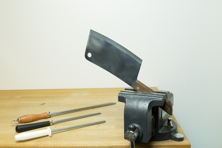 Cleaver pressed by a vise with sharpening steels on the side Imagens - 78565792