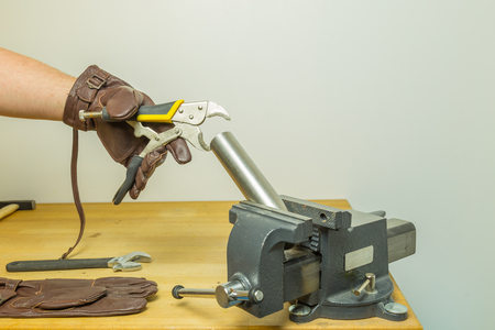 vise: Caucasian hands in brown leather gloves fixing a pipe with a circular flat cutting pliers wrench hold by a vise on a working bench Stock Photo