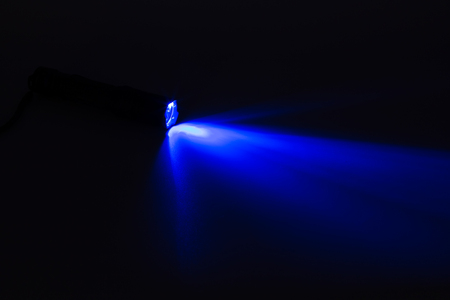 defuse: Blue light flash coming from a flashlight on the dark