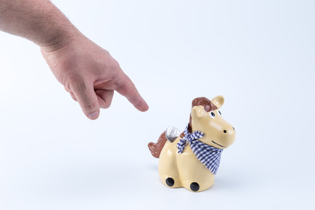 dept: Caucasian hand pointing a country horse piggy saving bank moneybox with a coin on its back hole Stock Photo