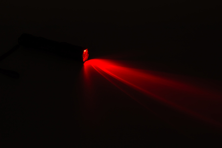 defuse: Red light flash coming from a flashlight on the dark