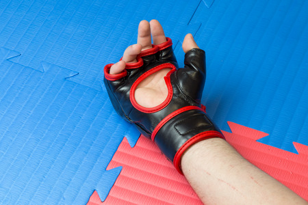 Concept of defeat, loss. Martial artist hand wearing mix mma open fingers gloves touching the tatami gym mats resembling tiredness, defeat, fatigue, exhaustion.