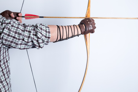 Side view of an archer wearing open fingers leather gloves, checked shirt, and arm guard, drawing a traditional english longbow with a red feather medieval arrow on it isolated on white background