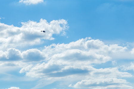 Blue sky with sculpted clouds on the background with real tinny helicopter flying on it